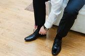 Man lacing up his black dress shoes — Stock Photo