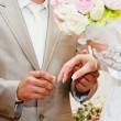 Groom putting a ring on bride's finger during — Stock Photo