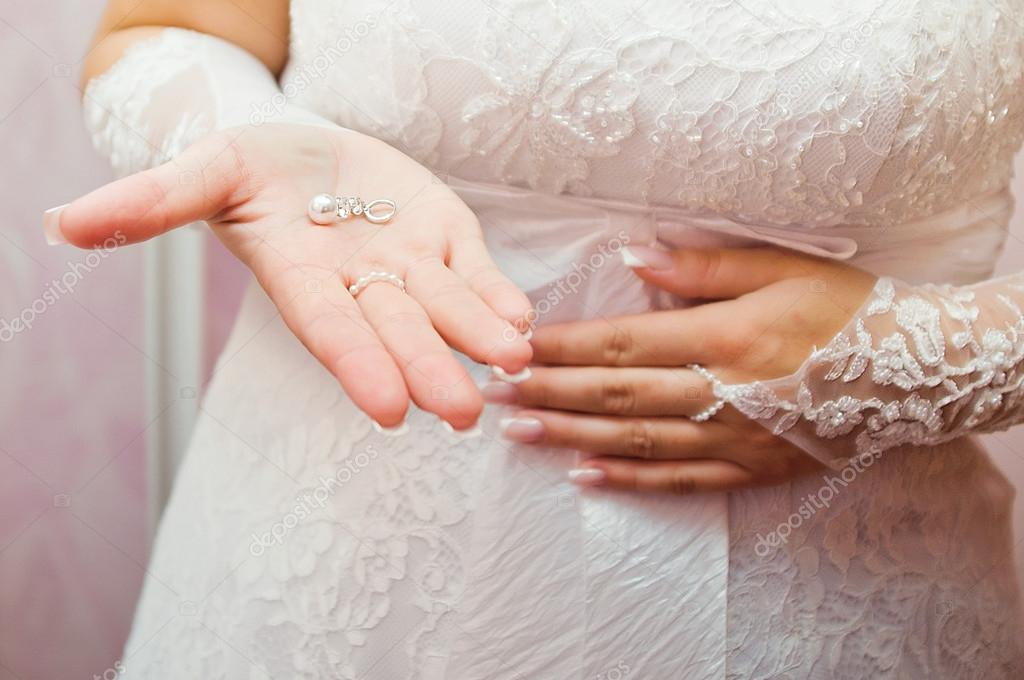 Ear ring on a hand at the bride — Stock Photo #19610459