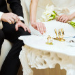 Stock Photo: Bride and groom signing wedding documents.
