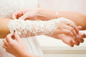 Bridesmaid helping bride to put on glove — Stock Photo