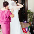 Friend helping bride get into dress - Stock Photo
