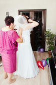 Friend helping bride get into dress — Stock Photo
