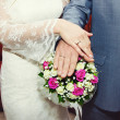 Stock Photo: Hands of the bride and groom lying on the bridal bouquet