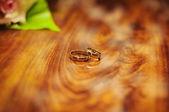 Un par de anillos de boda oro en capas el uno al otro. — Foto de Stock