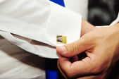 A groom putting on cuff-links — Stock Photo
