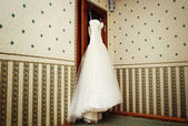 White Wedding dress hanging on a shoulders — Стоковое фото