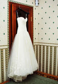 White Wedding dress hanging on a shoulders — Photo
