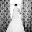 Image of beautiful bride standing at window — Stock Photo
