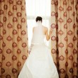 Image of beautiful bride standing at window — Stock Photo #36482471