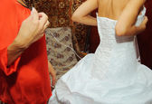 Helping the bride to put a wedding dress on — Stok fotoğraf