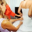 Stock Photo: Helping bride to put  wedding dress on