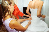 Helping the bride to put a  wedding dress on — Stock Photo