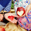 Woman's hand with apple, which cut a heart — Stock Photo
