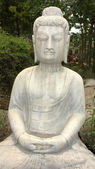 Ancient Buddha statue against green woods — Stockfoto