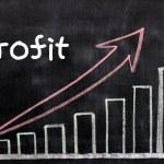 Charts of profit written with chalk on a blackboard — Stock Photo #9375559