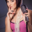 Stock Photo: Beautiful singer singing with a retro microphone