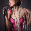 Beautiful singer singing with a retro microphone — Stock Photo #20147591