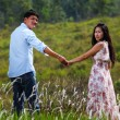 A Couple Walking Through A Grassland, holding hands — Stock Photo