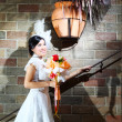 Elegant bride with wedding bouquet over brick wall — Stock Photo