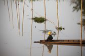 Native Asian fisherman sitting on the boat with bamboo — Stockfoto