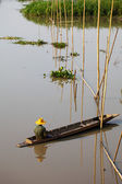 Native Asian fisherman sitting on the boat with bamboo — Foto Stock