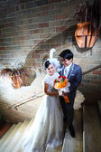 Beautiful wedding couple with bouquet in a castle — Stock Photo