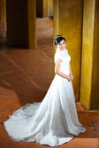 Romantic portrait of the beautiful bride near pillars — Stock Photo