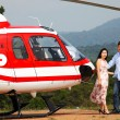 Happy loving couple traveling by helicopter and smiling — Stock Photo #37874663
