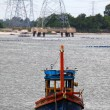 Wooden fishing boat and electrical tower in industrial area — Stock Photo #37883249