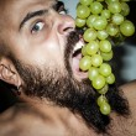Man with beard who eats voraciously grapes — Stock Photo #12701928