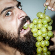 Man with beard who eats voraciously grapes — Stock Photo #12701930
