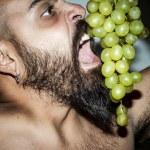 Man with beard who eats voraciously grapes — Stock Photo #12701931