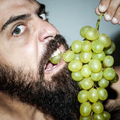 Man with beard who eats voraciously grapes — Stock Photo