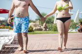 A young couple walking hand in hand in swimsuit — Stock Photo