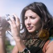 Beautiful girl with scarf and camera on the lawn — Stock Photo