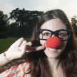 Royalty-Free Stock Photo: Clown girl with red nose at the park