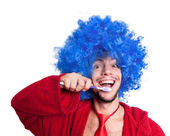 Crazy guy with a toothbrush, wig and bathrobe — Stock Photo