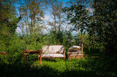 Old furniture abandoned in bucolic landscape — Stock Photo