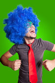 Funny dancing guy with blue wig green eyeglasses and red tie — Stock Photo