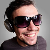 Smiling guy with headphones and sunglasses — Stock Photo