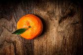 Mandarin with leaf on wood — Stock Photo