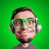 Człowiek marionetką słuchanie muzyki z duża głowa — Zdjęcie stockowe