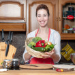 Beautiful housewife with basket of vegetables — Stock Photo