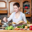 Beautiful housewife cooking vegetables with cookbook — Stock Photo