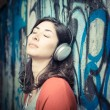 Beautiful stylish woman listening to music - Stock Photo
