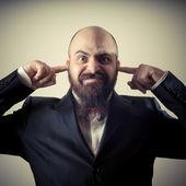 Funny elegant bearded man fingers in the ears — Stock Photo