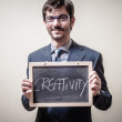 Businessman holding blackboard written creativity — Stock Photo