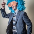 Funny businessman with big orange glasses and blue wig — Stockfoto #25404643