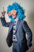 Funny businessman with big orange glasses and blue wig — Stock Photo